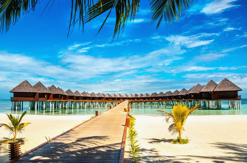 Ponte di legno che conduce ad un bungalow esotico sui precedenti di acqua azzurrata, Maldive fotografie stock