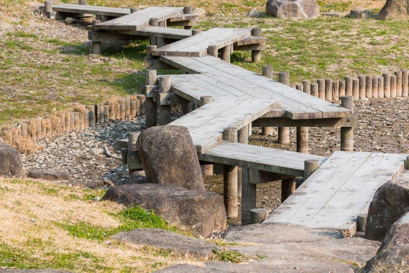 Ponte di legno che zigzaga sullo stagno asciutto con la siccità fotografia stock libera da diritti