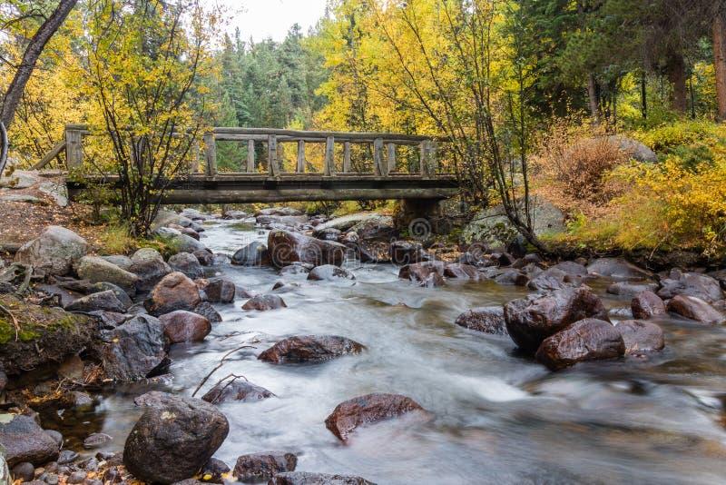 Ponte di legno del piede sopra la corrente fotografia stock libera da diritti