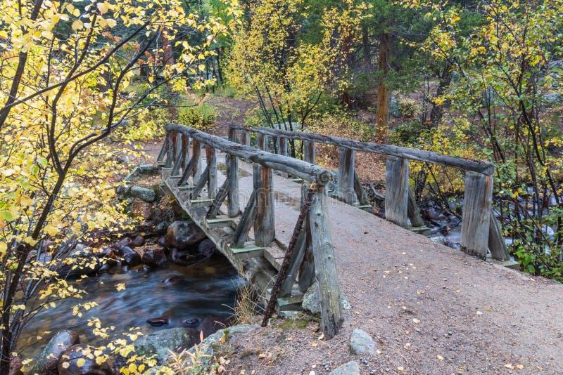 Ponte di legno del piede sopra la corrente immagini stock