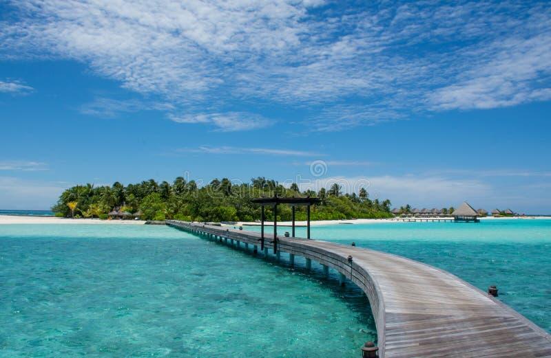 Ponte di legno lungo all'isola tropicale alle Maldive fotografie stock