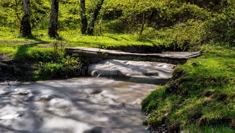 Ponte di legno sopra un piccolo fiume fotografia stock libera da diritti