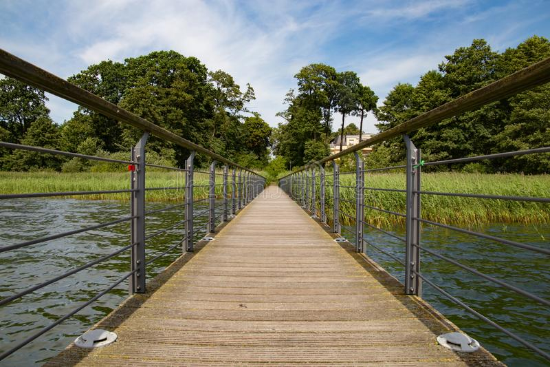Ponte di legno sulla prospettiva di sparizione del punto della foresta immagini stock