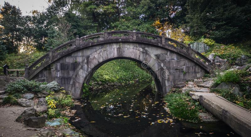 Ponte di pietra antico al parco fotografia stock