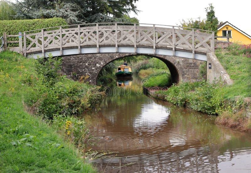 Ponte di pietra del piede sopra il canale di Monmouthshire e di Brecon in Galles del sud con narrowboat fotografie stock