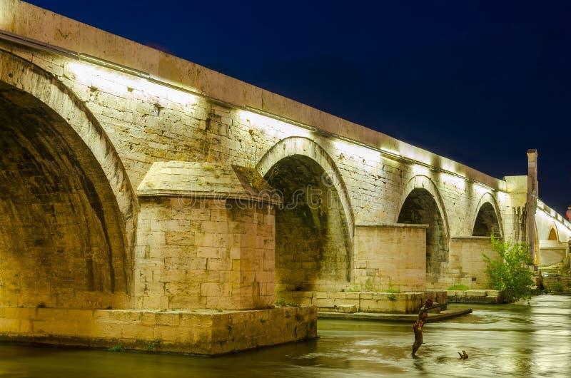 Ponte di pietra famoso alla notte a Skopje immagini stock