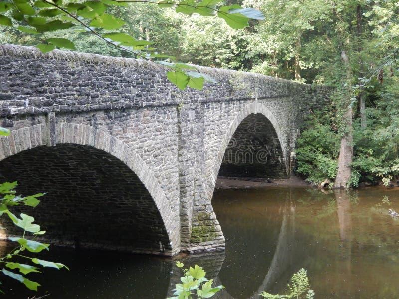 Ponte di pietra incurvato doppio sopra la corrente da sotto immagini stock libere da diritti
