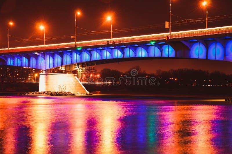 Ponte di Slasko-Dabrowski illuminato alla notte con la riflessione POLONIA, VARSAVIA fotografia stock libera da diritti