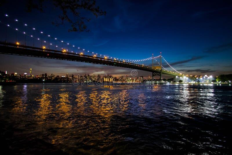 Ponte di Triborough sopra il fiume e Manhattan alla notte, New York fotografia stock