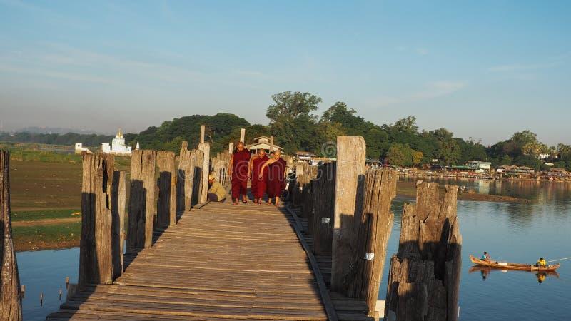 PONTE DI U-BEIN, AMARAPURA, MYANMAR 21 SETTEMBRE: Monaci buddisti sulla loro passeggiata quotidiana attraverso il ponte nelle ore immagine stock