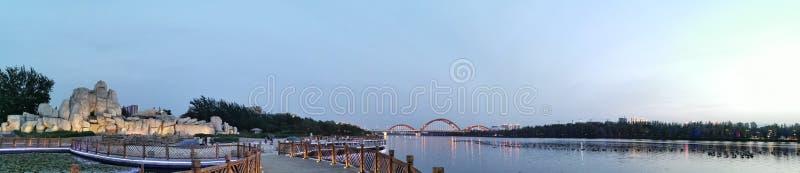A ponte do arco-íris na distância, no jardim ornamental próximo e no lago fotografia de stock royalty free
