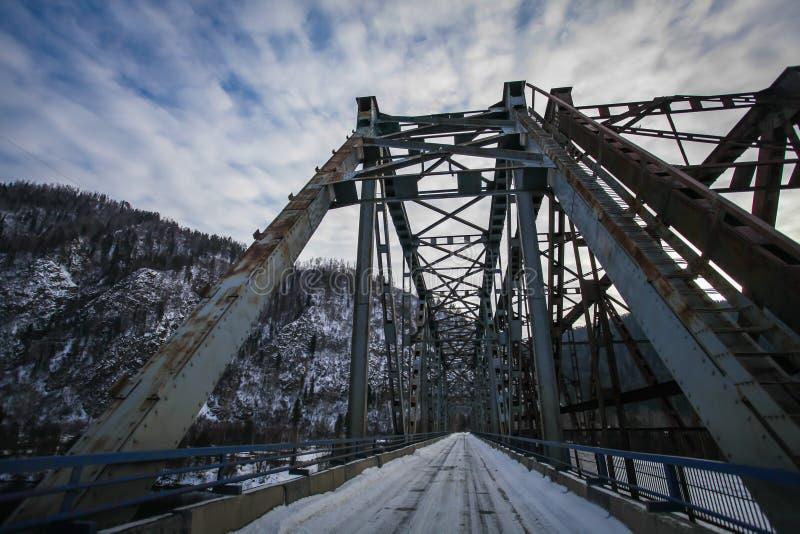 Ponte do carro entre montes nevado em um dia de inverno sombrio frio imagem de stock royalty free