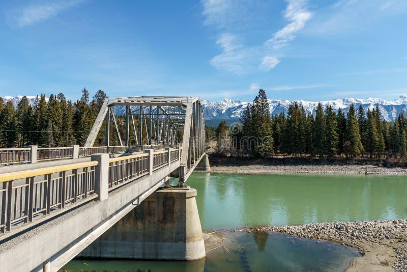 ponte do metal sobre o rio com água verde na mola com as montanhas no fundo fotografia de stock