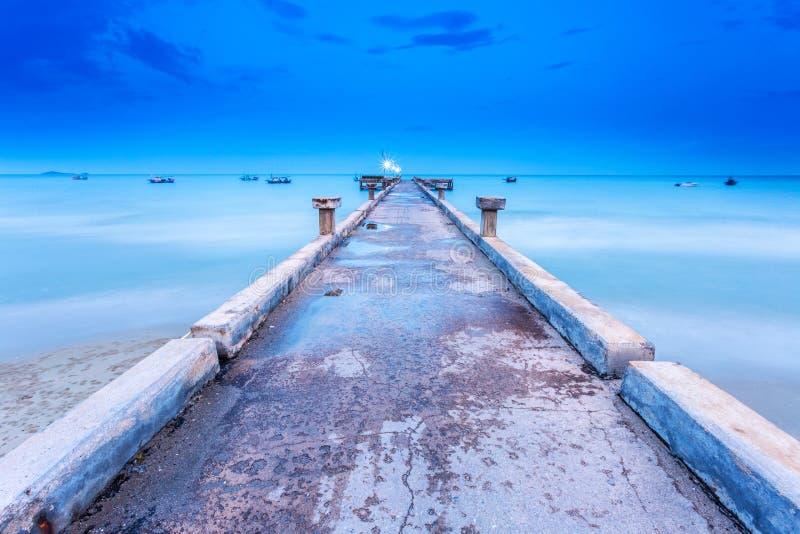 Ponte do molhe sobre ao mar no céu azul do verão para o barco e o navio Ressaca lisa e borrada da técnica longa da exposição por  foto de stock royalty free