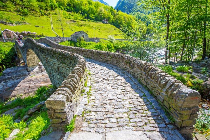 Ponte dobro da pedra do arco no dei Salti com cachoeira, Lavertezzo de Ponte, Verzascatal, Ticino, Suíça foto de stock