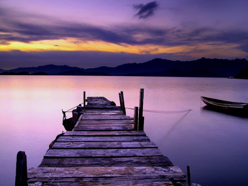 Ponte e bote de madeira do pé no por do sol fotos de stock royalty free