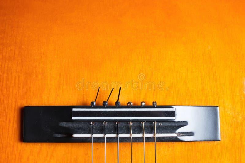 Ponte e cordas de uma guitarra amarela e alaranjada imagens de stock royalty free