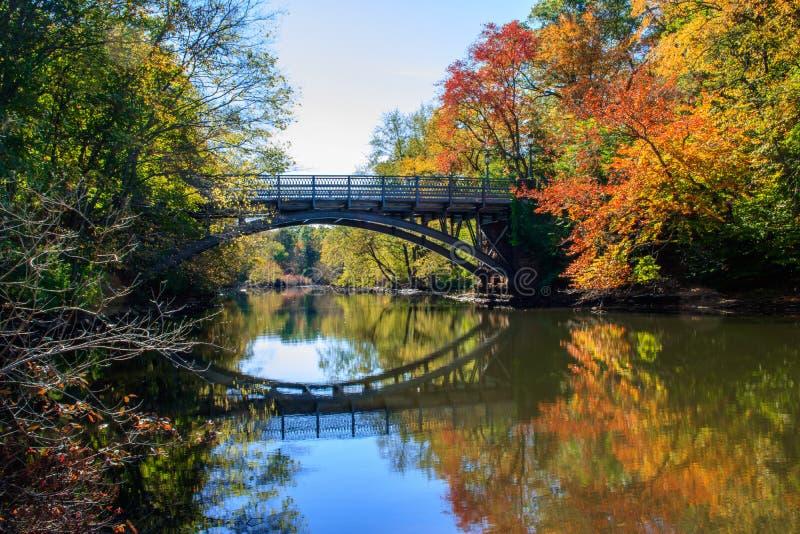 A ponte e a folhagem de outono refletiram no rio do moinho imagem de stock