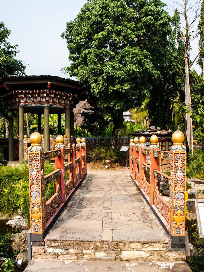 Ponte e gazebo tradizionali del Bhutan in giardino immagini stock libere da diritti