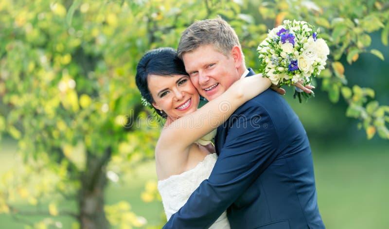 Ponte e noivo Pares felizes do casamento após a cerimônia de casamento em g fotos de stock royalty free