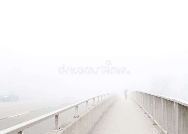 A ponte e o homem distante desvanecem-se na névoa fotografia de stock