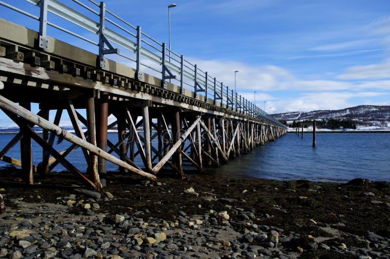 Ponte estreita longa do carro que conecta a ilha dois da ilha da baleia e do haak junto sobre o fiorde azul e o fundo nevado da m fotografia de stock royalty free