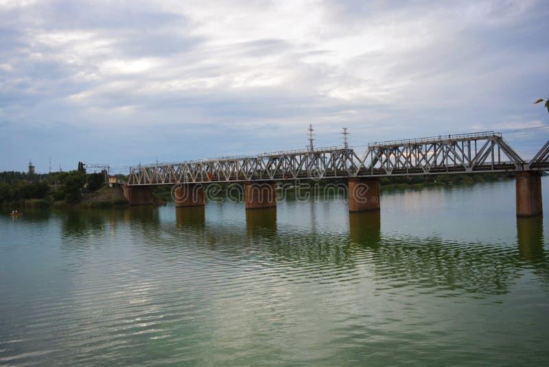 A ponte ferroviária cinzenta Samara sobre a superfície do rio Samara com uma bela paisagem, árvores verdes, arbustos e verde foto de stock
