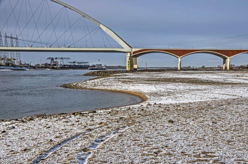 Ponte, fiume e spiaggia della città nell'inverno fotografia stock libera da diritti