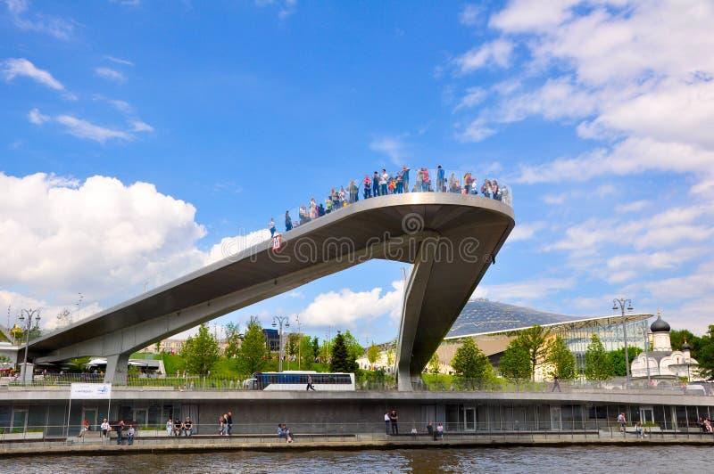 Ponte flutuante cheia de visitantes no parque de Zaryadye sobre o aterro de Kotelnicheskaya visto do rio Moscou fotos de stock