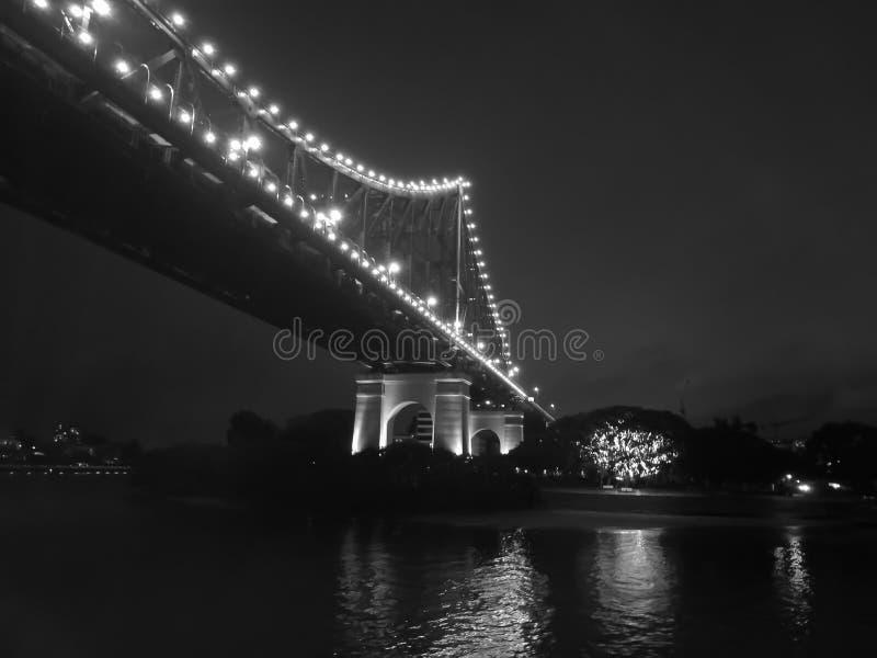 Ponte iconico di storia di Brisbane con i grattacieli della città alla notte in b immagini stock
