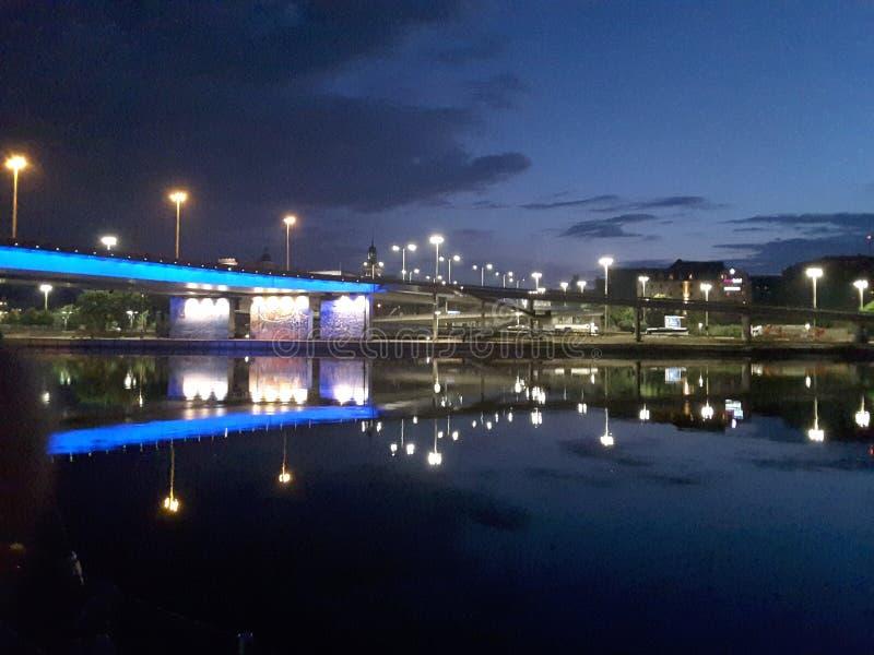Ponte illuminato sopra un fiume calmo in sera tardi fotografie stock libere da diritti