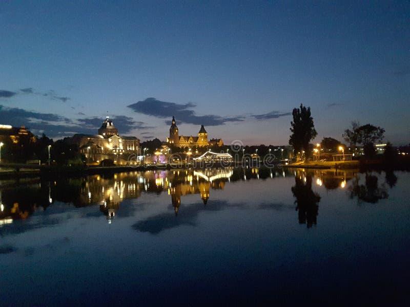 Ponte illuminato sopra un fiume calmo in sera tardi fotografia stock