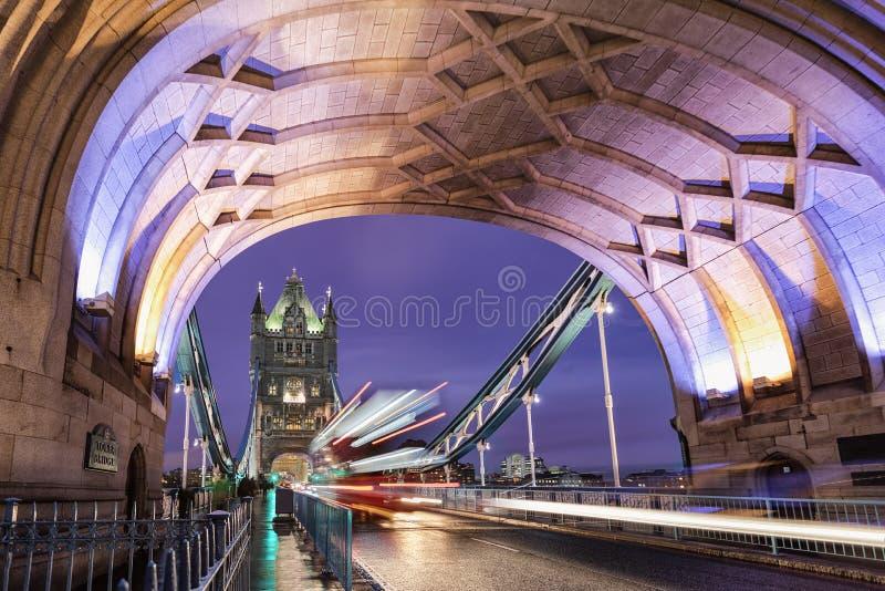 A ponte iluminada da torre com uma passagem pelo ônibus vermelho do ônibus de dois andares foto de stock
