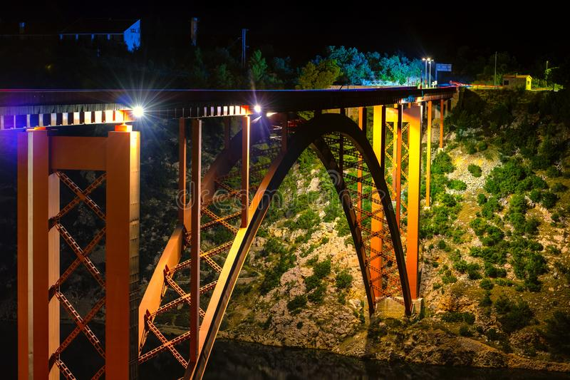 Ponte iluminada na noite, construção de aço do arco fotografia de stock