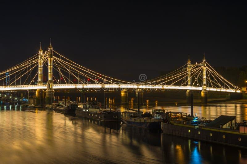Ponte iluminada na noite, Londres de Albert, Reino Unido imagem de stock