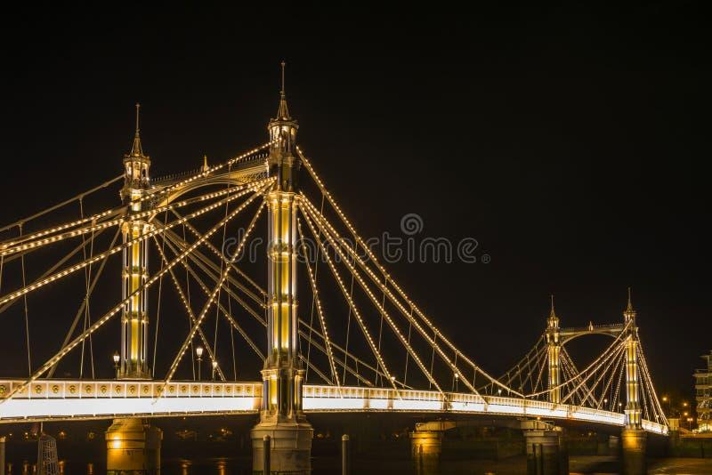 Ponte iluminada na noite, Londres de Albert, Reino Unido fotografia de stock