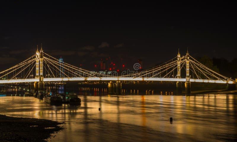 Ponte iluminada na noite, Londres de Albert, Reino Unido fotos de stock