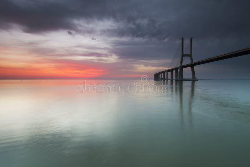 Ponte longa sobre Tagus River em Lisboa no alvorecer foto de stock