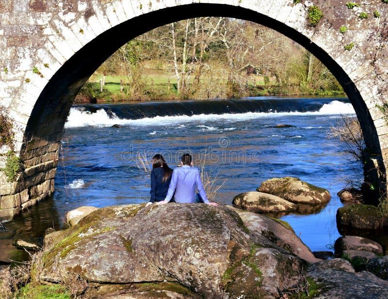 Ponte Maceira, España, el 16 de febrero de 2019 Un par que toma una rotura debajo de un puente Rocas, río con la cascada y bosque foto de archivo