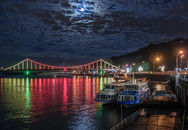 Ponte multicoloured de incandescência da cidade acima do rio e barcos no cais foto de stock