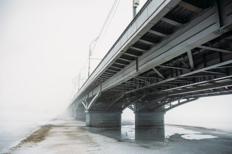 Ponte na névoa sobre o rio congelado no gelo e na neve Paisagem urbana misteriosa com névoa fotografia de stock royalty free