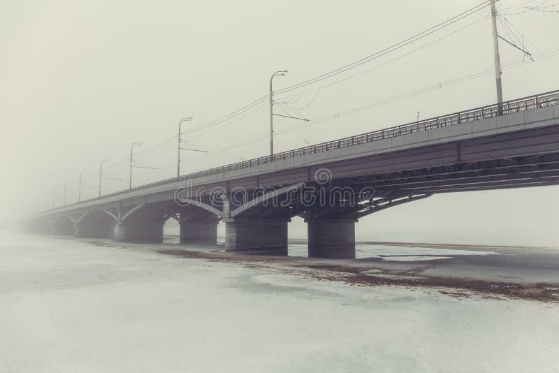 Ponte na névoa sobre o rio congelado no gelo e na neve Paisagem urbana misteriosa no dia nevoento, vintage tonificado fotografia de stock