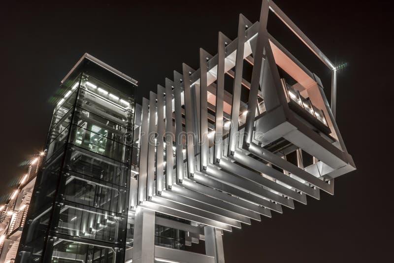 Ponte pedestre futurista moderna sobre o canal de água de Dubai na noite imagens de stock