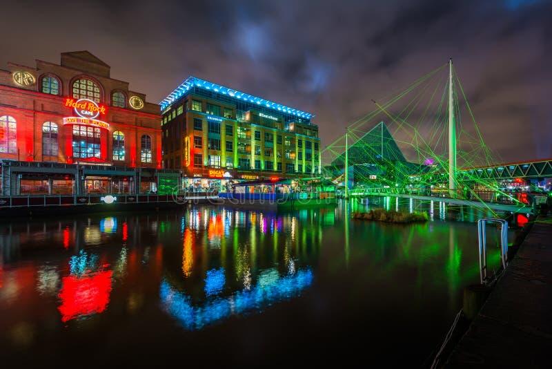 Ponte pedonale e costruzioni al porto interno alla notte, a Baltimora, Maryland fotografie stock