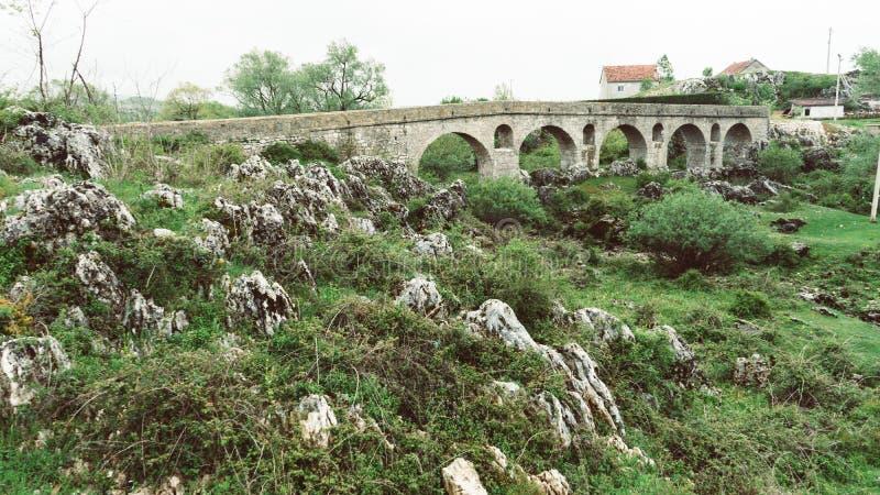 Ponte romana ( Rimski most) no ? a de Ilid? ?, Niksic Montenegro Ponte de pedra secada em uma vila pequena fotos de stock