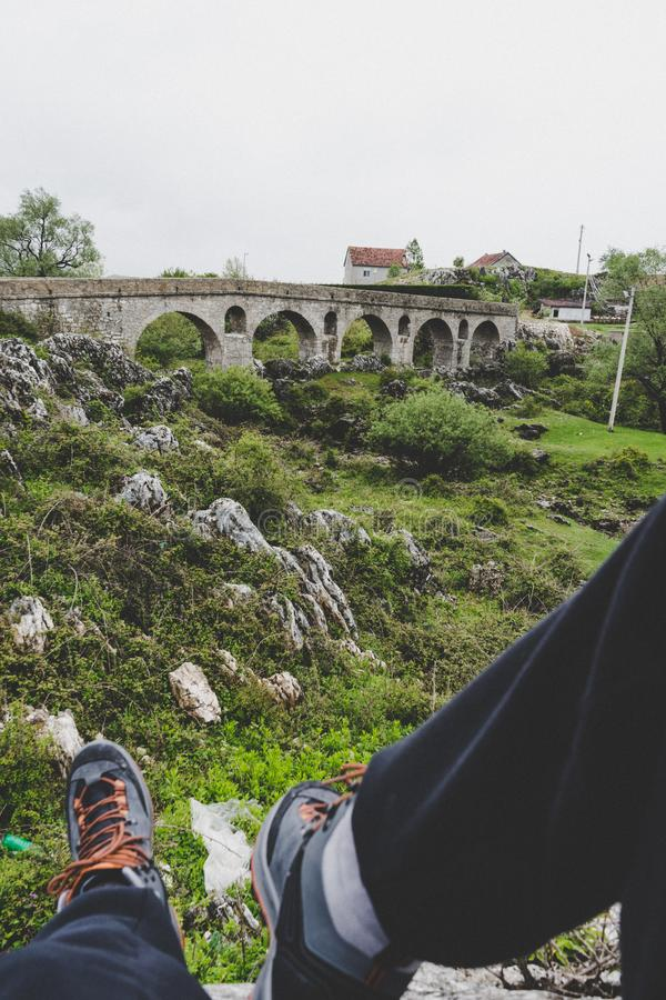 Ponte romano o vecchio ponte Ponte di pietra, parte di una strada romana Fiume asciutto Villaggio del Montenegro gambe maschii ne fotografia stock