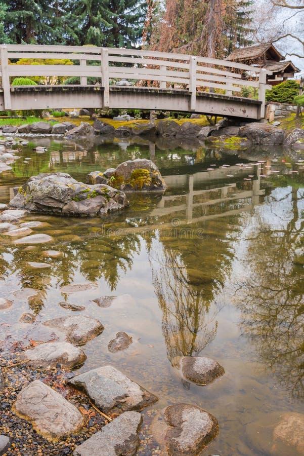 Ponte sobre a lagoa do koi e rochas no jardim japonês fotografia de stock