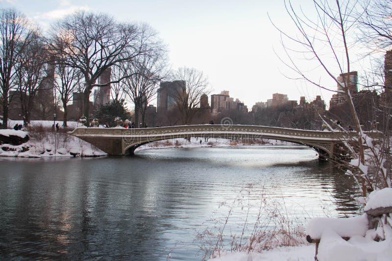 Ponte sobre o lago com neve no inverno antes do por do sol, Central Park da curva fotografia de stock royalty free