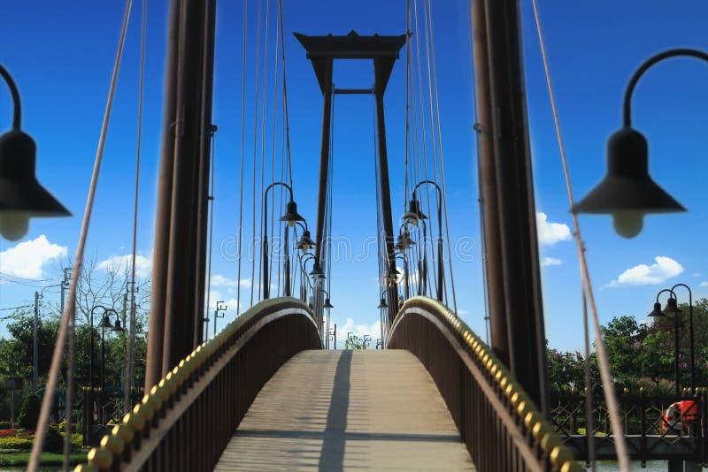 A ponte sobre o rio do trilho de madeira concreto do assoalho do parque em um céu azul reflete abaixo do rio imagem de stock royalty free