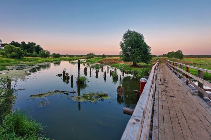 Ponte sobre um rio pantanoso no tempo do por do sol fotografia de stock